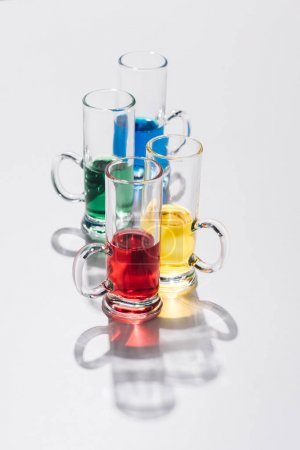 close up view of arranged alcohol cocktails in glasses on white backdrop
