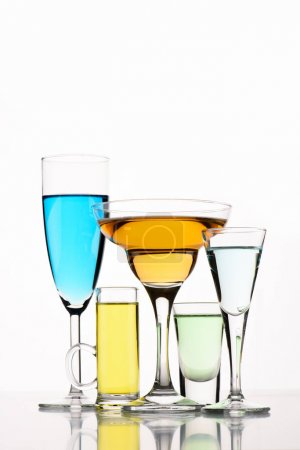 close up view of various alcohol cocktails in glasses on white backdrop