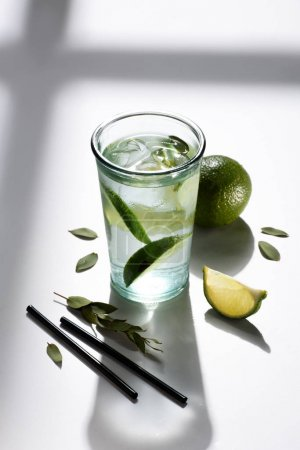 close up view of straws, glass of water with lime pieces and ice on white tabletop
