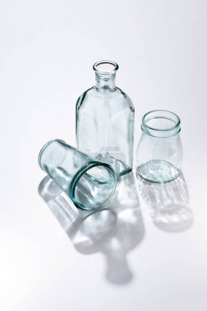 close up view of empty glassware and shadows on white surface