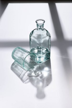 close up view of empty glass and bottle with water on white surface
