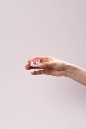 cropped shot of woman holding plastic container of pills isolated on grey