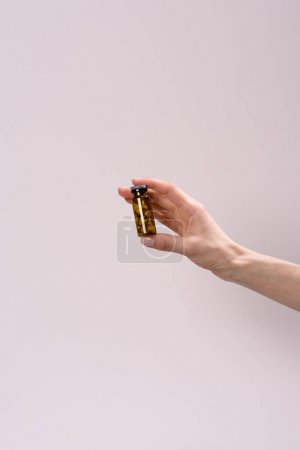 cropped shot of woman holding toned glass jar of pills isolated on grey