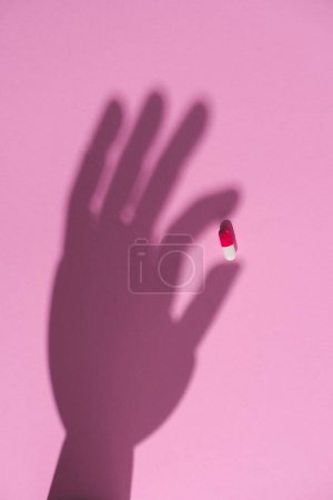 top view of shadow of hand holding drug capsule on pink surface