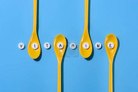 Photo pour Vue du dessus des cuillères et pilules en plastique jaune avec lettrage vitamine en rangée sur bleu - image libre de droit