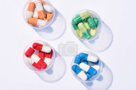 Photo for Top view of various colorful pills in plastic cans on white - Royalty Free Image