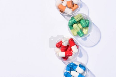 top view of various colorful pills in plastic bowls on white