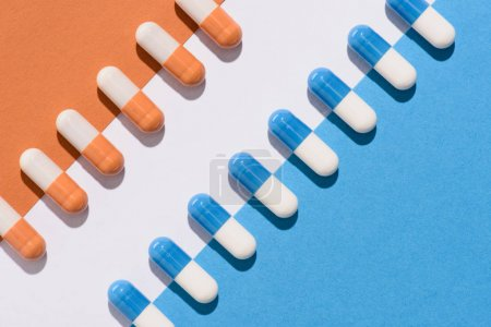 top view of blue and orange pills on colorful surface