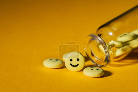 Photo for Close-up shot of pills with smiley faces and glass bottle on yellow - Royalty Free Image