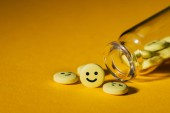 close-up shot of pills with smiley faces and glass bottle on yellow
