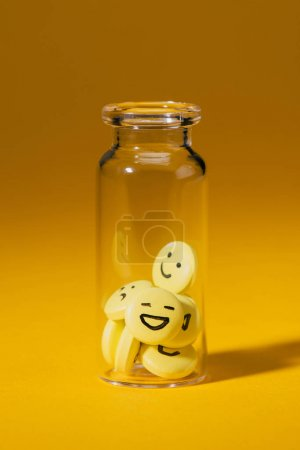 close-up shot of pills with smiley faces in glass bottle on yellow