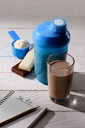 chocolate protein shake with energy bars and notebook with be fit sign on white wooden table