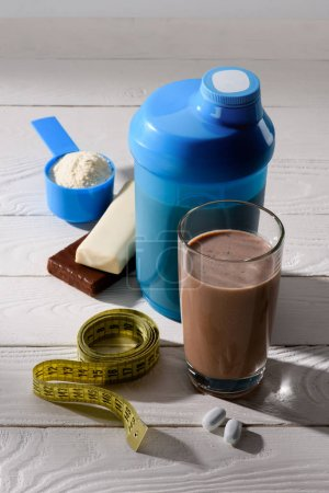 chocolate protein shake with measuring tape and energy bars on white wooden table