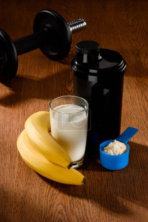 protein shake with dumbbell and bananas on wooden surface
