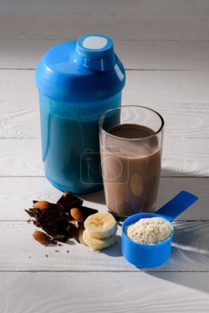 Photo for Shaker and glass of protein shake with almond, banana and chocolate on white wooden table - Royalty Free Image