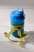 close-up shot of protein shaker tied with measuring tape on white wooden table