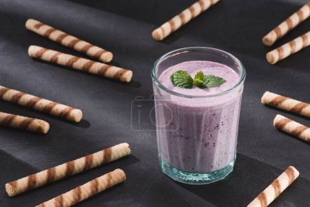 closeup view of berry smoothie with mint and sweet straws on table