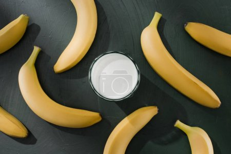 top view of glass with milkshake surrounded by bananas on table
