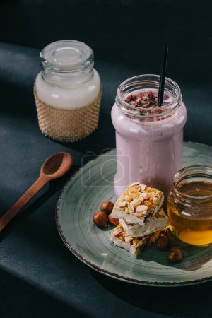 closeup view of berry smoothie with drinking straw, slices of energy bar, jam and walnuts on plate, spoon and bottle of yogurt on table
