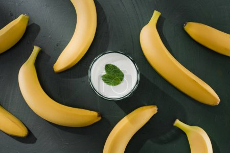 top view of bananas and milkshake glass with mint on table