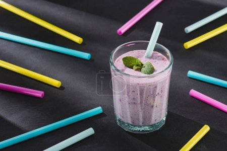 closeup image of drinking straws and glass of berry smoothie with mint
