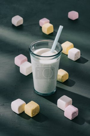 closeup view of milkshake with drinking straw and marshmallows on table