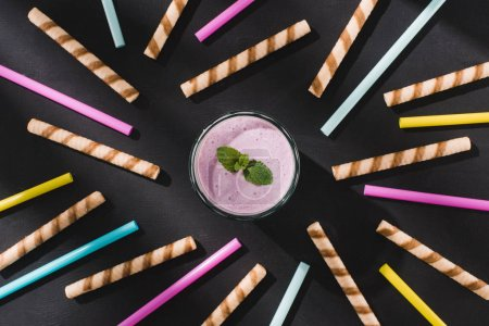 top view of berry smoothie with mint surrounded by drinking straws and sweet straws on table