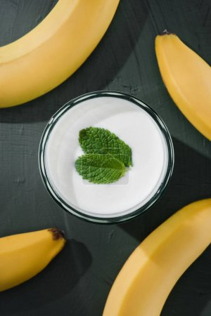 top view of bananas and milkshake with mint on table