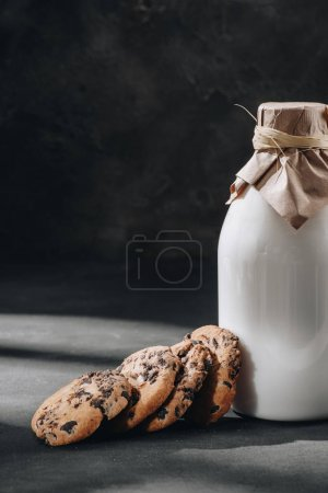 delicious chocolate-chip cookies with glass bottle of milk on black surface