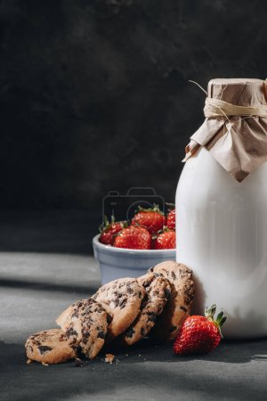 close-up shot of tasty chocolate-chip cookies with milk and strawberries