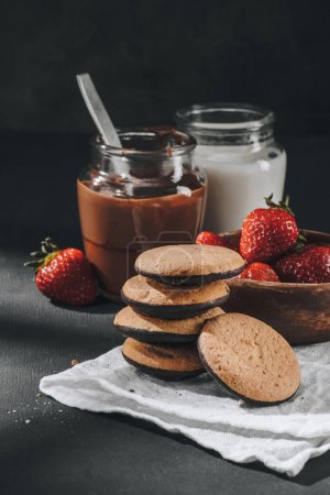 delicious stacked cookies with strawberries and jars of chocolate and milk