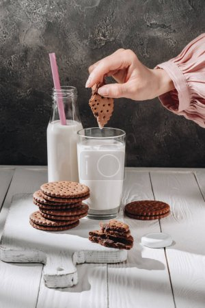 cropped shot of woman dipping chocolate cookie into glass of milk
