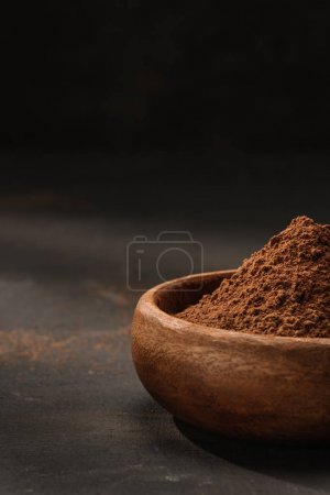cropped image of cocoa powder in wooden bowl on table