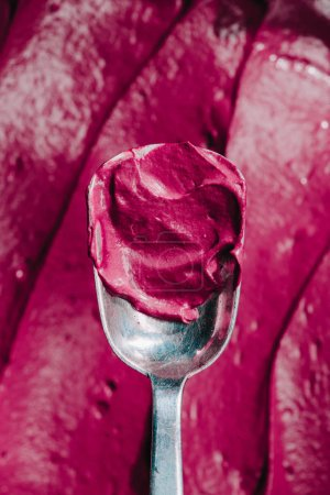 top view of spoon with tasty appetizing pink dessert