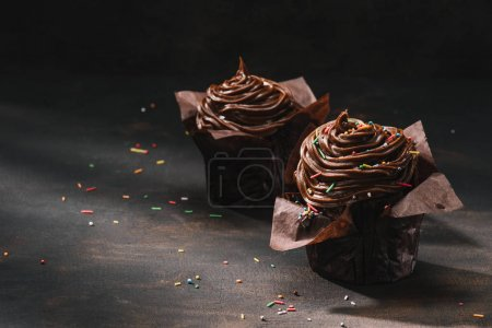 Yummy chocolate cupcakes with buttercream glaze and sugar spreading on table