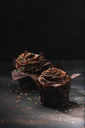 Appetizing chocolate cupcakes with buttercream glaze on table