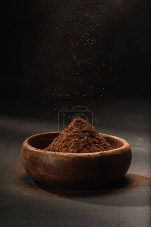 Photo for Cocoa powder in wooden bowl on tabletop - Royalty Free Image