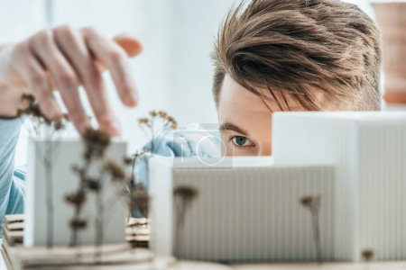 partial view of young architect looking at self made building model in office