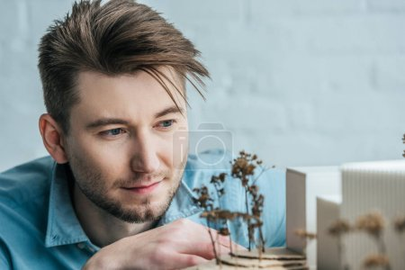 selective focus of architect looking at self made building model in office