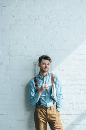 portrait of pensive architect with pencil and notebook looking away while standing against white brick wall