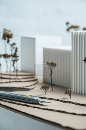close up view of stationery knife and modern building model on tabletop