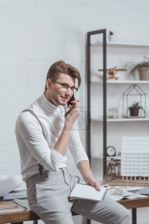 portrait of architect in eyeglasses with notebook talking on smartphone at workplace in office
