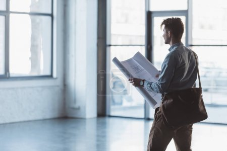 side view of architect with blueprint in hands standing in empty building