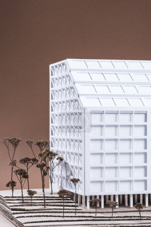close up view of white building model with miniature trees on brown backdrop