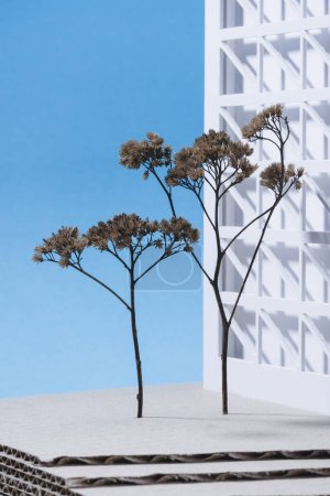 close up view of white building model with miniature trees on blue background