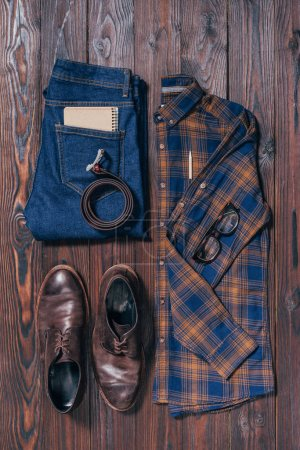 flat lay with male stylish shirt, shoes, jeans, eyeglasses and belt arranged on wooden surface