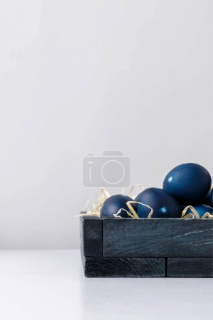 Illustration for Blue Easter eggs in wooden box on white surface isolated on grey - Royalty Free Image