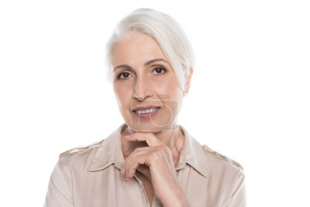 Photo for Close-up portrait of beautiful smiling senior lady with hand on chin looking at camera - Royalty Free Image