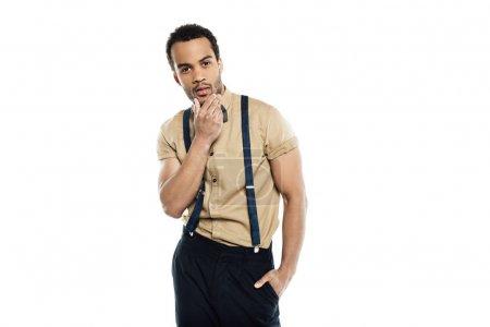 Photo pour Jeune homme afro-américain pensif touchant son visage et regardant la caméra isolé sur blanc - image libre de droit