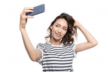 Photo pour Femme élégante souriante prenant selfie sur smartphone isolé sur blanc - image libre de droit